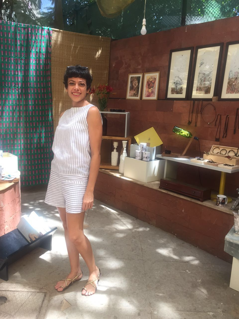 Artist and Designer Ratna Gupta poses in front of her stall - RESTORIES, at the Vintage Garden, Bandra, Mumbai. She is wearing a playsuit designed by Pallavi Dhyani of Three.