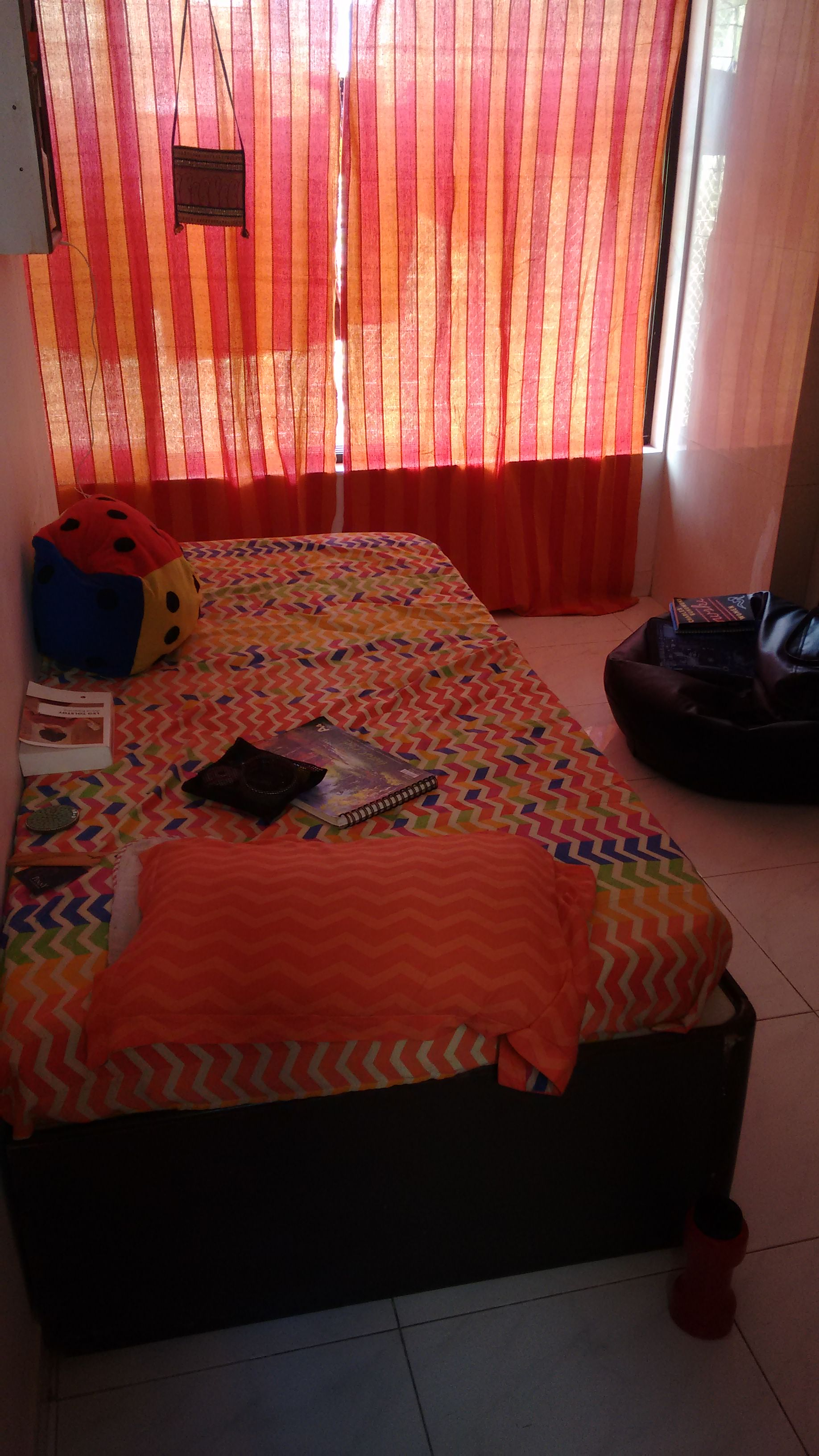 My very orange room with a messy bed and scattered books | Chai High is an Indian Fashion Blog started by Shivani Krishan