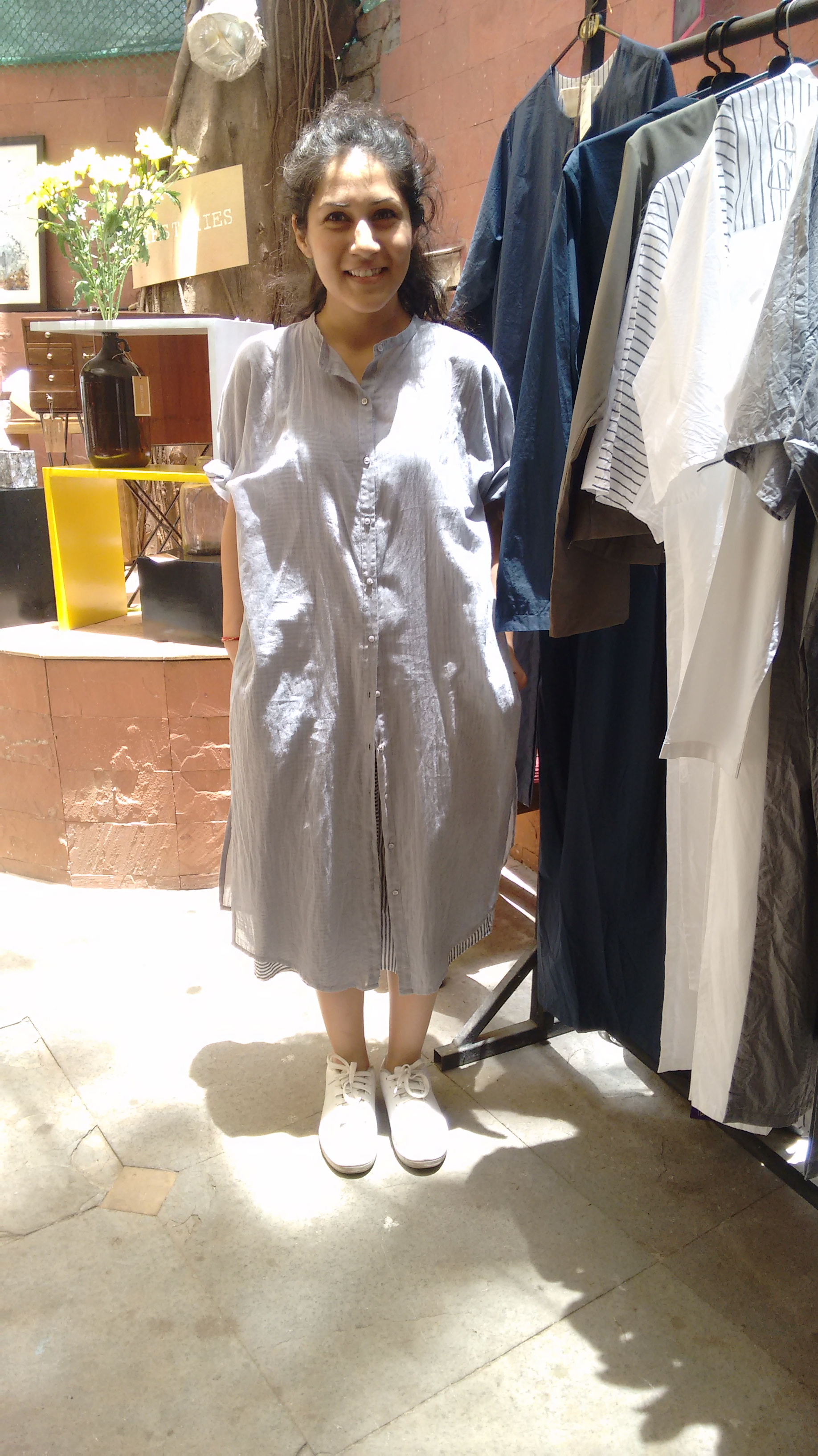 Pallavi Dhyani wearing her own creation from THREE at the Vintage Garden. Her collection is fabricated from cotton and linen and has plenty of stripes. She wears her THREE shirt dress with a striped under-slip and white sneakers. At the Vintage Garden, Bandra, Mumbai.